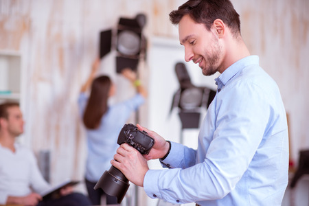 gladness: Pleasant smiling delighted handsome man holding photo camera and working in photo studio while expressing gladness