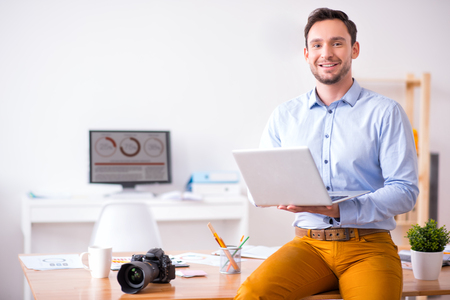 gladness: Cheerful content smiling handsome man sitting on the table and holding laptop while expressing gladness