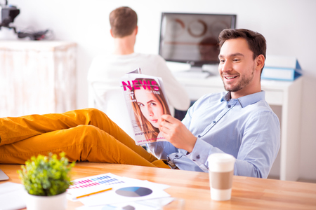 Positive content handsome man holding his legs on the table and sitting in the chair while reading womans magazine