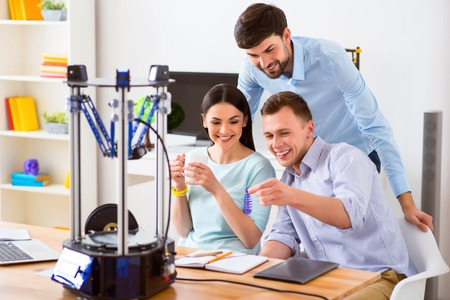 model fish: Pleasant smiling delighted students sitting at the table and smiling while holding model of fish printed on 3d printer Stock Photo