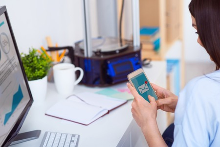 3d printer: Pleasant beautiful woman sitting at the table and holding cellphone while 3d printer standing in the background