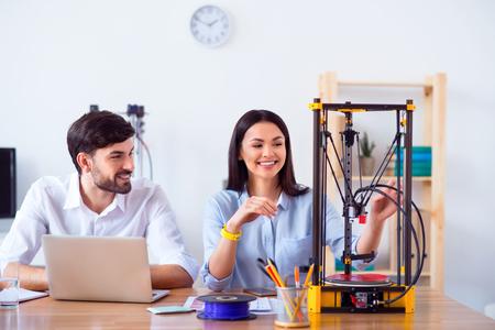 테이블에 앉아 기쁨을 표현하면서 3d 프린터를 사용하는 쾌활한 기쁘게 미소 짓는 동료
