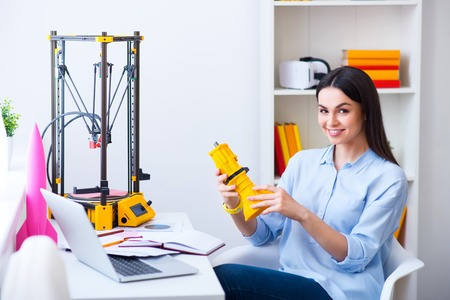 gladness: Pleasant beautiful smiling delighted woman sitting at the table and holding model printed on the 3dprinter while expressing gladness