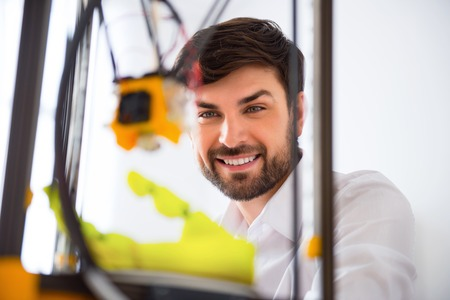 gladness: Cheerful delighted smiling man using 3d printer and expressing gladness Stock Photo