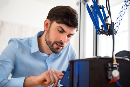 3d printer: Pleasant concentrated man sitting at the table and using 3d printer while being involved in work