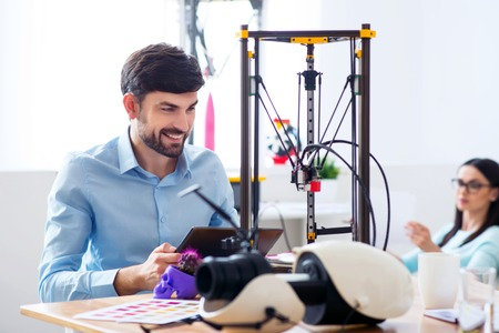 3d printer: Positive content smiling man using tablet and working with 3d printer while his colleague resting in the background
