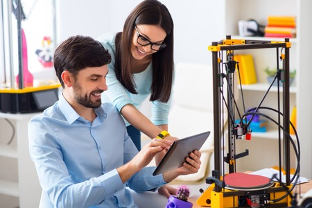 3d printer: Cheerful delighted smiling colleagues using tablet and expressing joy while 3d printer working on the table