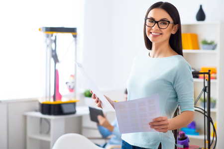 gladness: Cheerful smiling beautiful woman holding papers and expressing gladness while her colleague sitting in the background