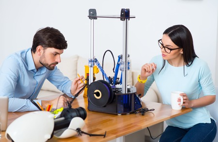 3d printer: Pleasant serious involved colleagues sitting at the table and working with 3d printer Stock Photo