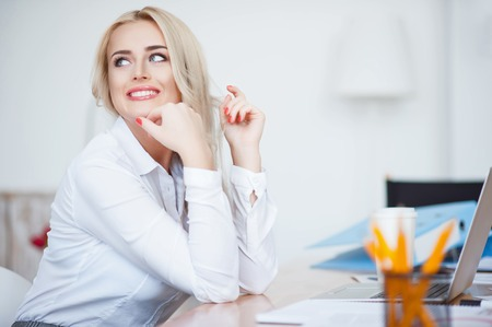 sufficient: Self sufficient person.  Cheerful content charming woman smiling and sitting at the table while expressing gladness in the office Stock Photo