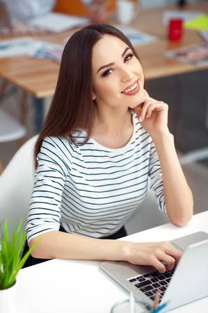 glad: Young beauty.  Cheerful delighted attractive smiling woman sitting at the table and working on the laptop while feeling glad Stock Photo