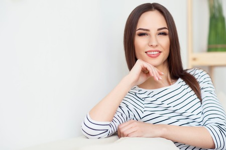 strong chin: Strong glance. Pleasant magnetic delighted woman holding her hand on the chin and sitting on the couch while looking at you Stock Photo