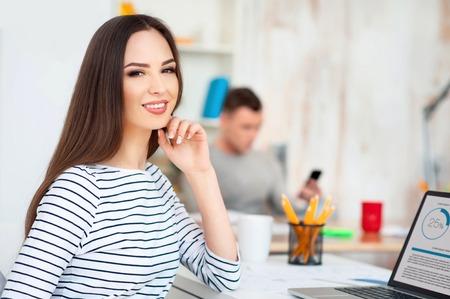 diligente: trabajador diligente. sonriente positivo bella mujer alegre que se sienta en la mesa y trabajar en la computadora portátil mientras que su colega está involucrado en el trabajo en el fondo