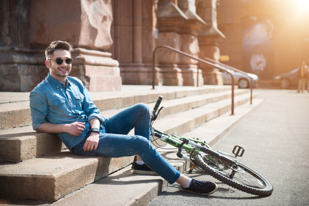 gladness: Express your emotions. Cheerful content smiling young man leaning on the footsteps   near his bicycle  and resting while expressing gladness