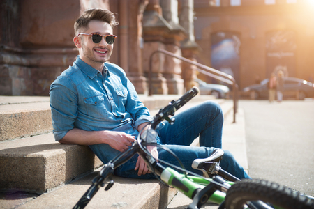 gladness: Full of joy.  Cheerful content smiling guy leaning on the footsteps   near his bicycle  and resting while expressing gladness