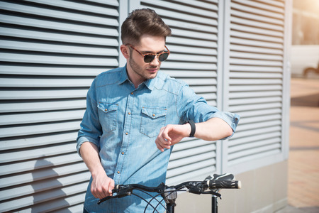 tempo: Follow your tempo. Pleasant  handsome guy looking at his wrist watch and holding bicycle while going to ride it