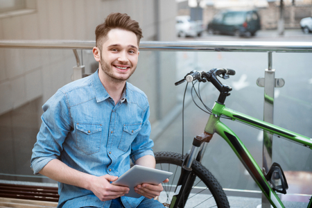 expressing joy: Modern generation.  Cheerful positive smiling young man sitting on the bench and holding tablet while expressing joy Stock Photo