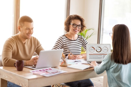 diligente: trabajadores diligentes. Agradables colegas positivos encantados sentado en la mesa y computadoras port�tiles mientras se trabaja en la oficina