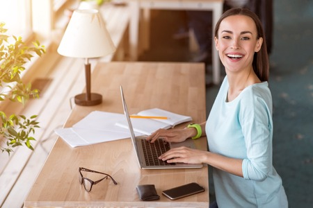 overjoyed: On the edge of positivity. Overjoyed smiling beautiful woman sitting at the table and using laptop while working in the office
