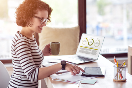 stay beautiful: Stay in positivity. Pleasant delighted beautiful woman drinking coffee and using laptop while sitting at the table Stock Photo