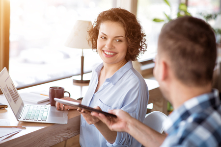 overjoyed: Here you are.  Overjoyed delighted smiling woman at the table and working on the laptop while getting tablet from her male colleague Stock Photo