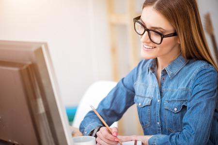 diligente: trabajador diligente. Agradable deleitó hermosa mujer sonriente sentado en la mesa y tomando notas mientras se trabaja en el ordenador