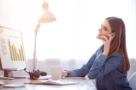 brigt: Enticed in work. Delighted smiling beautiful woman sitting at the table and talking on cell phone while making notes