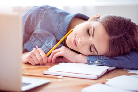 facial features: Deserve some rest. Pleasant delighted beautiful woman sitting at the table and sleeping on its surface after working in the office Stock Photo