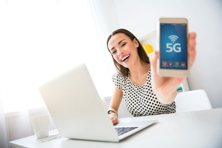 gladness: New innovation. Cheerful delighted beautiful smiling woman sitting at the table and holding cell phone while expressing gladness