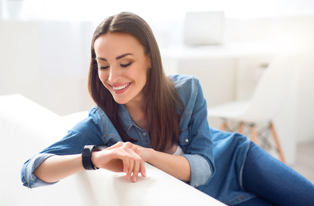 gladness: Involved in gladness. Positive delighted charming woman sitting on the couch and looking at her wrist watch while resting