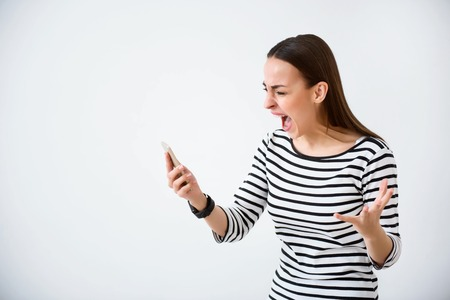 cheerless: Reveal your emotions. Emotional angry cheerless woman holding cellphone while standing isolated on white background Stock Photo