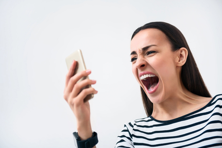 cheerless: On the edge of fury.  Emotional bad tempered  cheerless woman holding cell phone and screaming while standing isolated on white background