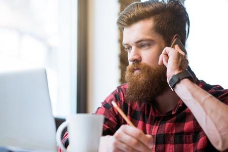 diligente: trabajador diligente. Agradable concentr� hombre barbudo hermoso que se sienta en la mesa y mirando a la pantalla de la computadora port�til mientras se habla por tel�fono celular