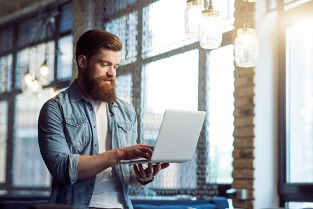 pleasant emotions: Share your emotions. Pleasant cheerful bearded man holding laptop and using it while standing in the office