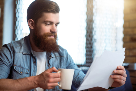 activate: Activate your brain. Pleasant cheerful content bearded man sitting at the table and working with papers while drinking coffee