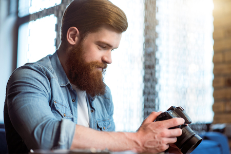 pics: Nice pics. Pleasant cheerful smiling bearded man sitting at the table and holding photo camera while expressing gladness