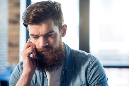 cheerless: Out of temper. Moody handsome bearded man holding cell phone and  talking on it while feeling cheerless