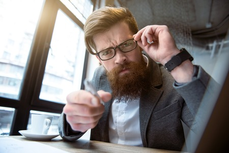 glance: Furious glance. Emotional  brutal man sitting at the table and touching his glasses while pointing you
