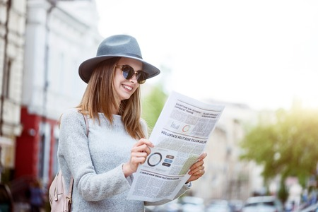 articles: What is up. Smiling and merry young woman reading some articles in a newspaper while being in a bid modern city