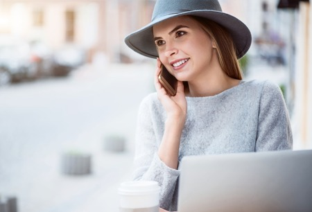 meaningful: Meaningful call. Smiling and content young woman making a phone call and using a laptop while sitting in a cafe and drinking nice coffee Stock Photo