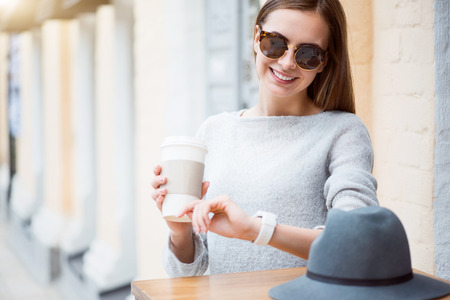 to be pleasant: Be on time. Smiling and pleasant young woman drinking nice coffee in a cafe and looking at her smart watch while waiting at her friends