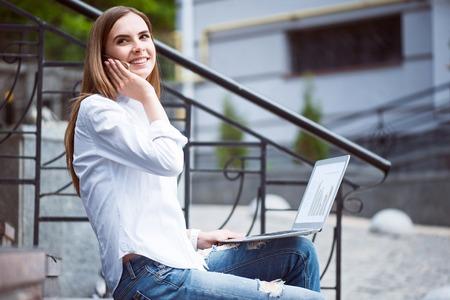 Wees bereikbaar en bereik. Glimlachende en positieve jonge vrouw gebruikend laptop en sprekend per mobiele telefoon terwijl het zitten op de treden
