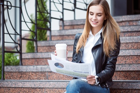 articles: Modernity.  Smiling and cheerful young woman reading some articles in a newspaper and drinking coffee while sitting on the stairs Stock Photo