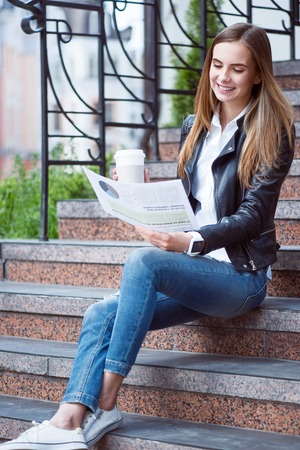 articles: My lifestyle.  Happy and cheerful young woman reading some articles in a newspaper and drinking coffee while sitting on the stairs Stock Photo