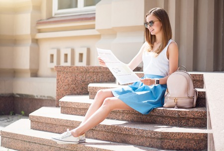 articles: Up to date of the latest news. Positive and cheerful young woman reading some articles in a newspaper while sitting on the stairs and being in a very good mood Stock Photo
