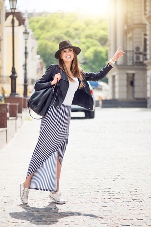 hailing: Hailing a cab.  Positive and very cheerful modern young woman hailing a taxi being in a big city