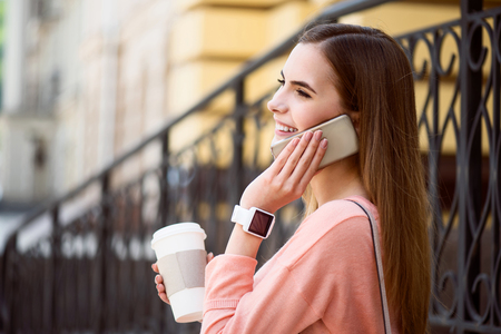important phone call: Important call.  Smiling and happy modern young woman speaking per cell phone and drinking coffee while being outside