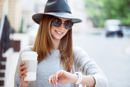 hurry up: Hurry up. Cheerful and glad modern young woman drinking nice coffee while being outside and looking at her smart watch