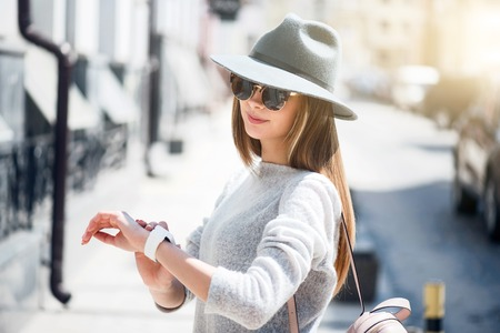 time flies: Time flies.  Confident and merry young woman looking at her smart watch while being outside and waiting for her friend