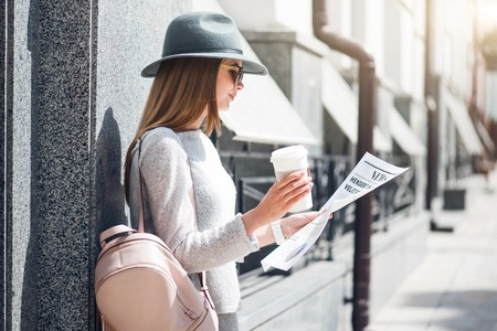 articles: Interesting news.  Confident and glad modern young woman reading some articles in a newspaper and drinking coffee while being outside Stock Photo